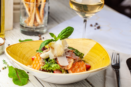 Foto de Caesar salad with salmon. mix of salads, cherry tomatoes, parmesan cheese, basil. A dish in a ceramic plate is on a wooden table in a restaurant. A glass of white wine is on the table. selective focus - Imagen libre de derechos