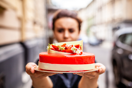 Foto de The girl on the street in her hands holds a cake of mousse, covered with a mirror glaze, on top of the cake the decor of strawberries, raspberries and white chocolate. - Imagen libre de derechos