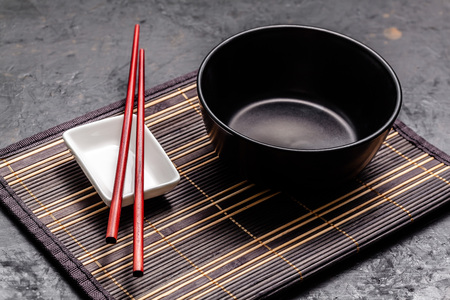 Photo pour Empty Japanese dishes. A black ceramic bowl for Chinese noodles or Thai soup lies on a bamkuk rug. White saucepot for soy sauce and red Chinese sticks on a black background. Top view, copy space - image libre de droit