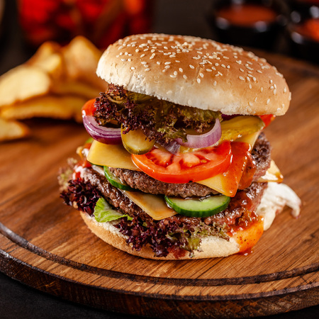 Photo pour American cuisine concept. A large homemade burger with a double pork and veal meat patty, tomato, cucumber, lettuce, and cheese. Closeup, background image - image libre de droit