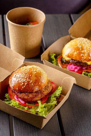 Foto de Street food. Meat cutlet burgers are in paper boxes. Food delivery. - Imagen libre de derechos