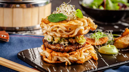 Photo for Pan-Asian cuisine concept. Ramen Chinese rice noodle burger, chicken and pork cutlet and salad, with wasabi sauce. Background image. Serving dishes with french fries. copy space - Royalty Free Image