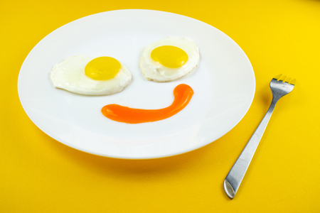 Foto de traditional breakfast of two fried eggs. Fun face from food. Plate with eggs on a yellow background. Concept image of breakfast, healthy eating - Imagen libre de derechos