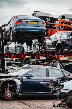 Foto de Damaged cars waiting in a scrapyard to be recycled or used for spare part - Imagen libre de derechos