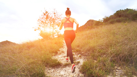 Young athletic woman running on mountain trail. Sunset Workout in Nature.