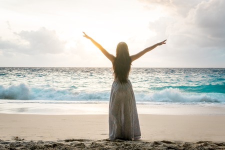 Photo for Woman in long dress with raised arms standing on beach and looking to ocean - Royalty Free Image