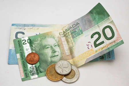 A close up of a selection of Canadian currency, including a 20 and a 5 dollar bill, a loonie, a twoonie, a quarter and a penny.