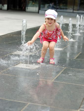 Happy beautiful girl playing with fountain in front of building