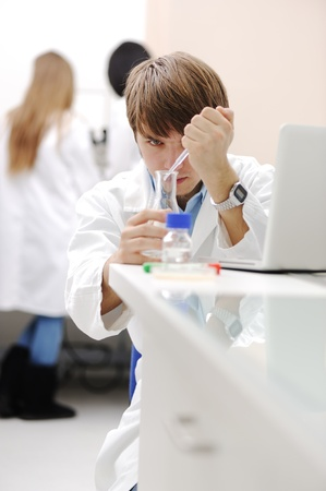 Young medical scientist working in modern lab, research with tubes and notebook