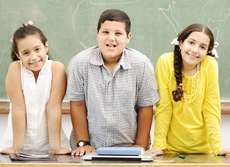 Three happy children standing at board, posing beside the table