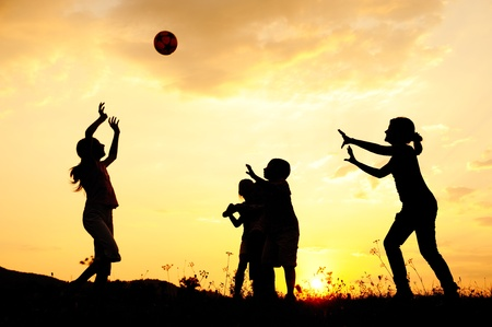 Photo pour Silhouette, group of happy children playing on meadow, sunset, summertime - image libre de droit