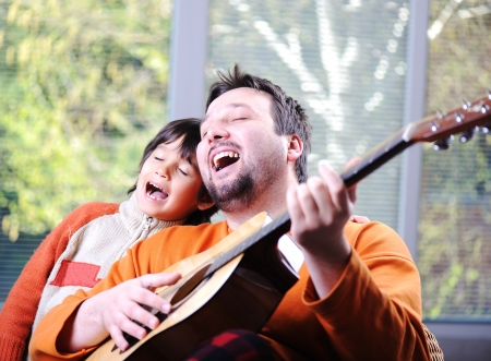 Photo for Father and son playing guitar at home - Royalty Free Image