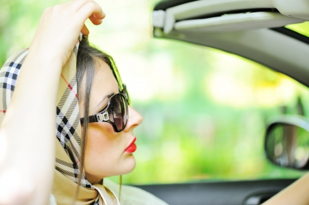 Young woman wearing headscarf driving a car