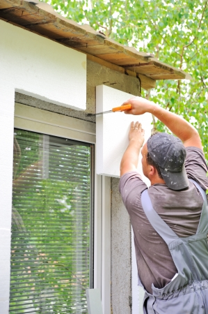 Construction worker applying insulation over exterior wall of house