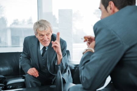 Business people talking  while boss is finger pointing