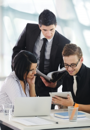 Three business people working at office with paperwork using tablet and laptop