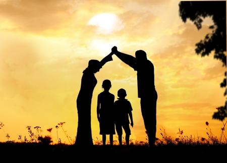 Foto de Silhouette, group of happy children playing on meadow, sunset, summertime - Imagen libre de derechos