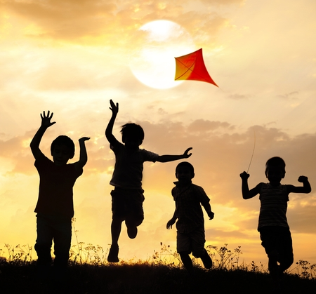 Group of happy children running and playing with kite on meadow at sunset summer time