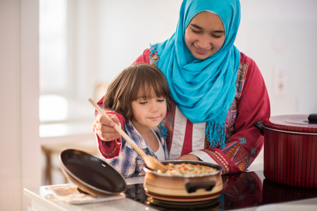 Foto de Arabic young woman with little kid in kitchen - Imagen libre de derechos