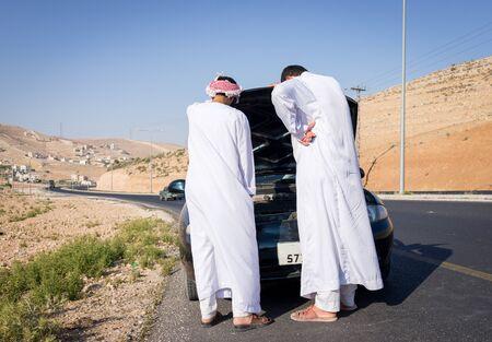 Photo pour Two young Arab men having car issue on the road - image libre de droit