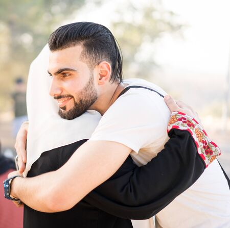 Photo for Muslim young man hugging his mother - Royalty Free Image