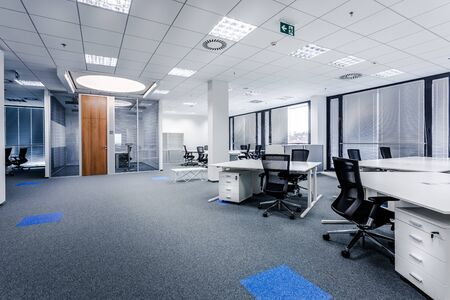 Photo pour Part of ordinary office room decorated in modern style with meeting room,large windows with blinds,carpeting,ventilation,escape signs,white furniture (tables, shelves, drawers) and dark office chairs. - image libre de droit