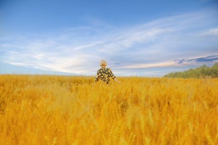 Photo pour Young beautiful blonde woman standing on a wheat field against dramatic sky background.  - image libre de droit