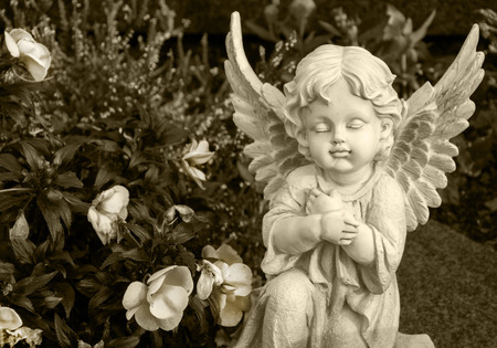Photo for angel made of clay sitting on a grave surrounded by flowers - sepia colored - Royalty Free Image