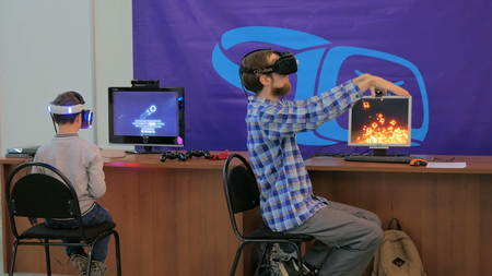 NIZHNIY NOVGOROD, RUSSIA - JANUARY 28, 2017: Exhibition of modern technologies. Virtual reality game. Young man using virtual reality glasses. VR