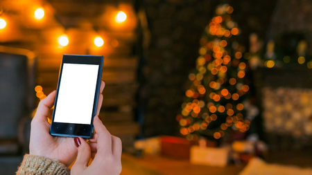 Woman looking at vertical smartphone with white blank screen at night. Christmas holiday bokeh background. Mockup, template, xmas and technology concept