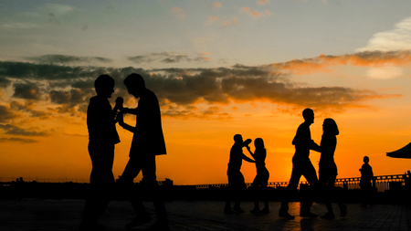 Photo pour Unrecognizable people silhouette learning how to dance - on city embankment at sunset. Street dance, romantic and urban culture concept - image libre de droit