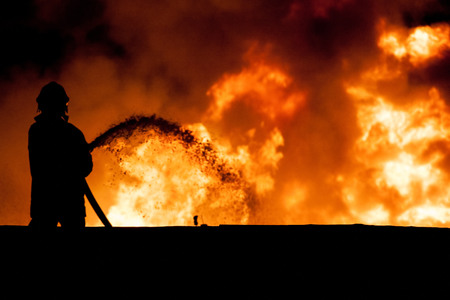 Photo pour Fireman working in the night at the explosion - image libre de droit