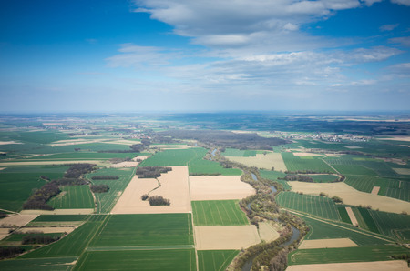 Aerial view of the large green field in spring season