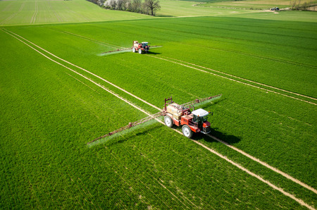 Photo pour Aerial view of the tractor spraying the chemicals on the large green field - image libre de droit