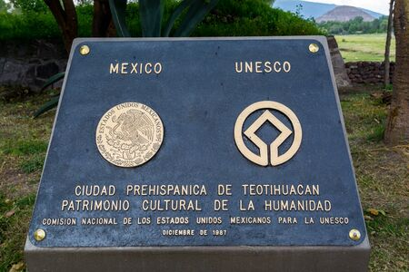 UNESCO sign at the Ruins of the architecturally significant Mesoamerican pyramids and green grassland located at at Teotihuacan, an ancient Mesoamerican city located in a sub-valley of the Valley of Mexico