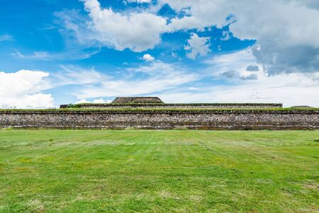 Ruins of the architecturally significant Mesoamerican pyramids and green grassland located at at Teotihuacan, an ancient Mesoamerican city located in a sub-valley of the Valley of Mexico