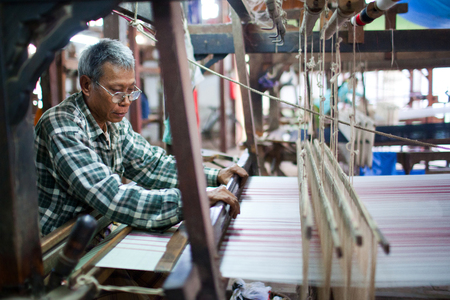 AMARAPURA, MYANMAR - JANUARY 11: Burmese worker poses for a photo at work in workers in textile mill on January 11, 2011 in Amarapura, Myanmar