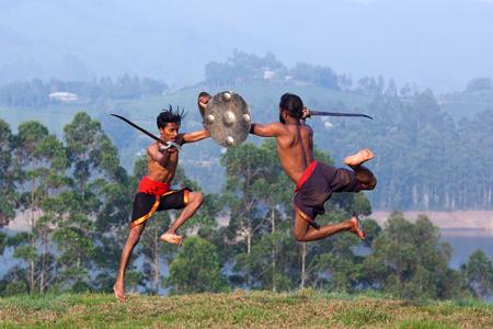Photo pour Indian fighters performing weapon combat during Kalaripayattu marital art demonstration in Kerala, South India - image libre de droit
