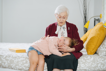 Photo pour Senior lady spending quality time with her great granddaughter. Restless naughty little girl bod bored trying to take a nap and doesn't make it easy. - image libre de droit