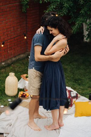 Photo for Middle-aged happy couple in love is dancing together during a picnic on lawn in their courtyard, behind a brick fence. They are standing very close to each other, hugging. - Royalty Free Image