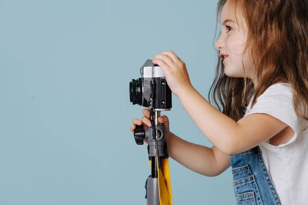 Photo for Little preschooler girl with brown wavy hair is taking an image with a vintage mirrored camera, fixed on a tripod. Over blue background. Side view. - Royalty Free Image