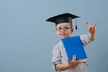 Cute smiling little ginger boy in glasses, wearing student hat holds stack of books in hands over blue background. Half length. He's making rock-n-roll gesture, to show he's cool.
