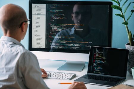 Photo for Bald caucasian programmer in glasses is sitting behind the desk, in front of two black screens, laptop and monitor, looking closely, analysing code lines. He's very attentive and focused. - Royalty Free Image