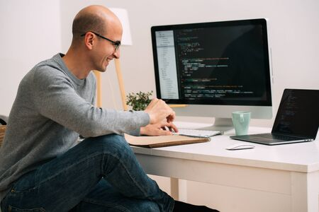 Photo for Bald caucasian programmer in glasses is sitting behind the desk, in front of two black screens, laptop and monitor, analysing code lines. He's laughing cheerfully about something. - Royalty Free Image