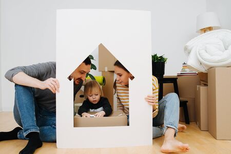 Photo for Cute little boy playing with toy model car inside a house resembling frame, held by his parents. Mother and father looking at him with love. Moving to a new home concept - Royalty Free Image