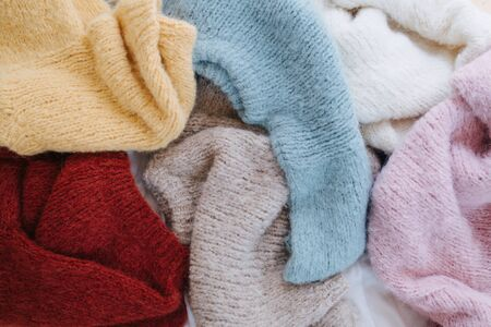 Photo pour Six unfolded evenly placed multi-colored soft fluffy knitted sweaters lie on the floor. Laundry day. Top view. - image libre de droit
