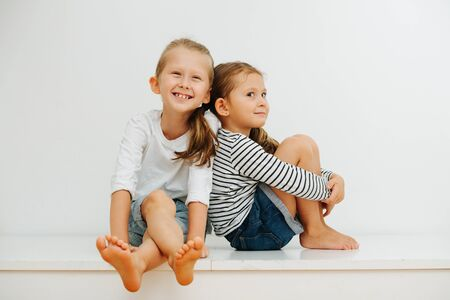 Photo for Funny little barefoot siblings sitting on a table with their legs up. Over white wall. Both wearing jeans shorts and long-sleeves. Boy is cheerful and girl is giving a perky look for camera. - Royalty Free Image
