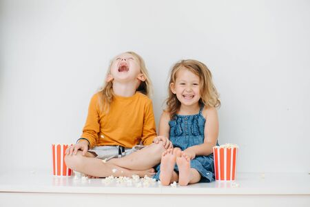 Photo pour Misbehaving little barefoot siblings sitting on a table with their legs up. Over white wall. They are eating pop-corn and playing with it, throwing it in the air. Boy making demonic laugh. - image libre de droit