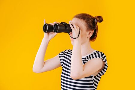 Photo for Girl in search with binoculars in hand, studio portrait on yellow background - Royalty Free Image