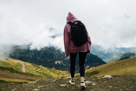 Photo for Young woman in mountains covered with short grass and trees, low clouds hanging around her. She's wearing hoodie, yoga pants and backpack, Enjoying the view. - Royalty Free Image